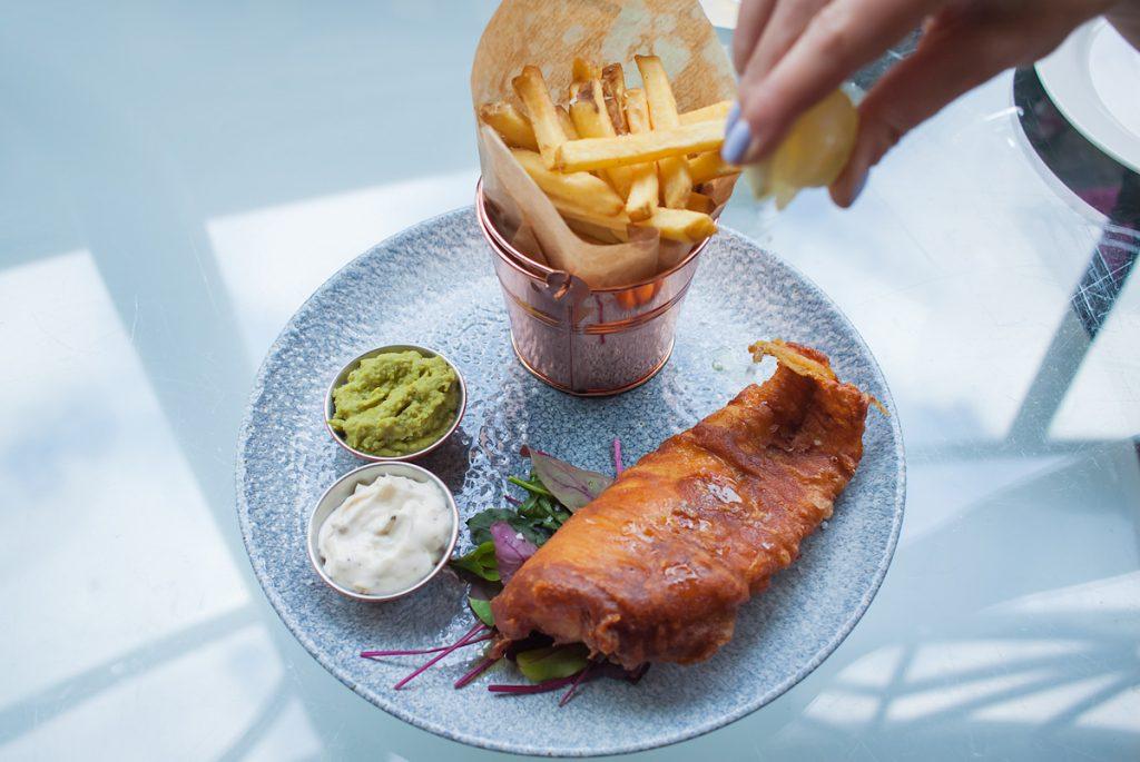 Kultowe Fish and Chips podane z pure z zielonego groszku, sosem tatarskim oraz chrupiącymi frytkami.