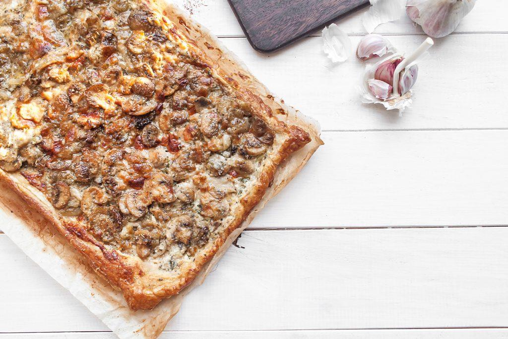tarta na ciescie francuskim z pieczarkami, karmelizowana cebula i serami